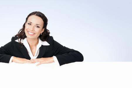 letreros: Feliz sonriente joven empresaria mostrando la señal, en ropa de estilo de negocios, área de copyspace en blanco para lema o mensaje de texto Foto de archivo