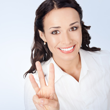 three: Happy smiling young businesswoman in white business style clothing, showing three fingers