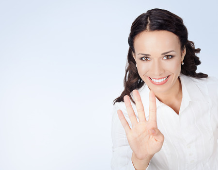 one woman: Happy smiling young businesswoman in white business style clothing, showing four fingers, with blank copyspace area for slogan or text message Stock Photo