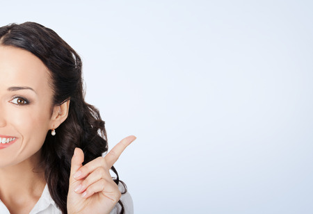 business style: Happy smiling young businesswoman in white business style clothing, showing blank copyspace area for slogan or text message Stock Photo