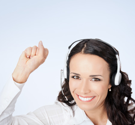handsfree phone: Portrait of happy smiling cheerful gesturing customer support phone operator in headset in white business style clothing Stock Photo