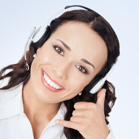 handsfree phones: Portrait of happy smiling cheerful customer support phone operator in headset with call me gesture in white business style clothing, with copyspace Stock Photo