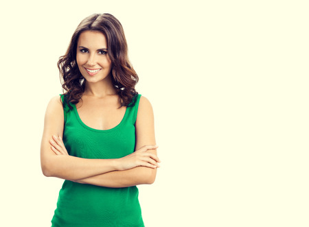 green clothes: Portrait of young happy smiling brunette woman in smart green casual clothing, with crossed arms, with blank copyspace area for slogan or text