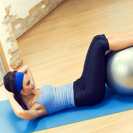 fit ball: Cheerful brunette woman doing fitness exercises with fit ball, indoors Stock Photo