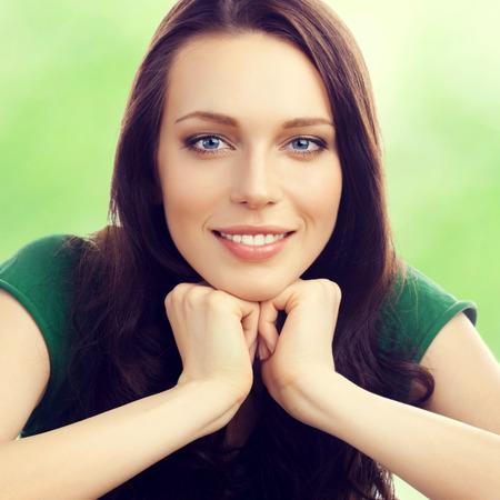陽気な笑みを浮かべて美しい若いブルネットの女性、屋外の肖像画