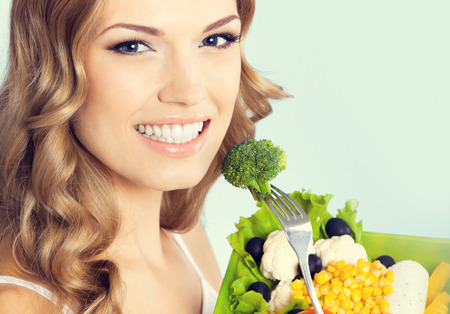 woman eating: Portrait of cheerful young lovely woman with healthy vegetarian salad with broccoli, against blue background. Healthy eating and dieting concept.