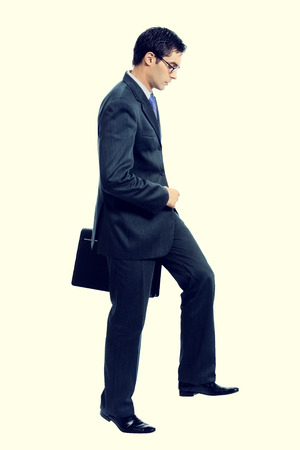 hasten: Walking young businessman with briefcase