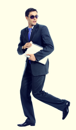 malefactor: Full body of young businessman or hacker in sun glasses with laptop running Stock Photo