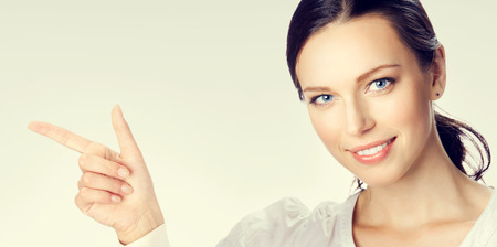copyspase: Portrait of happy smiling young businesswoman showing something or blank copyspase area for sign text message