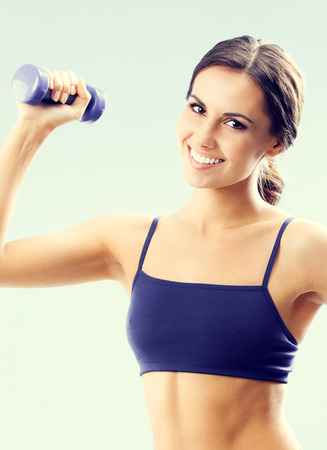 WOMAN FITNESS: Cheerful woman in fitness wear exercising with dumbbell
