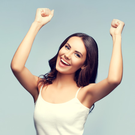 tank top: Portrait of cheerful gesturing smiling young woman in white tank top clothing Stock Photo