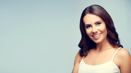 young women only: Portrait of beautiful cheerful smiling young woman in white tank top clothing, with blank copyspace area for text or slogan Stock Photo