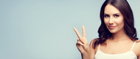 fingers on top: Beautiful young woman in white tank top clothing, showing two fingers or victory gesture, with blank copyspace area for text or slogan