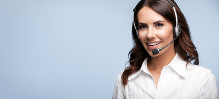 smiling customer support female phone operator in headset, against grey background. Consulting and assistance service call center.