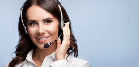 blank center: Portrait of smiling support female phone operator in headset, against grey background. Consulting and assistance service call center.