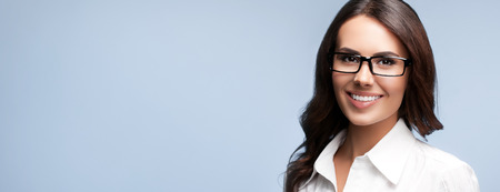 business attire teacher: Portrait of happy smiling brunette businesswoman in glasses, over grey background