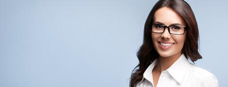 anteojos: Retrato de feliz sonriente morena de negocios en gafas, sobre fondo gris Foto de archivo