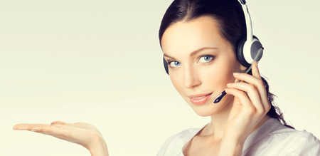 business support: Portrait of support phone operator in headset showing something or blank copyspace area for text or slogan