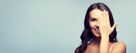 one eye closed: Concept photo of happy smiling young woman in white tank top clothing with one eye, closed by hand, covering part of her face, with blank copyspace area for text or slogan