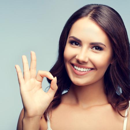 mujer alegre: Retrato de la mujer sonriente alegre joven que muestra gesto bien en la ropa blanca sin mangas