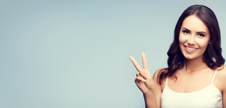 fingers on top: Portrait of beautiful young woman in white tank top clothing, showing two fingers or victory gesture, with blank copyspace area for text or slogan