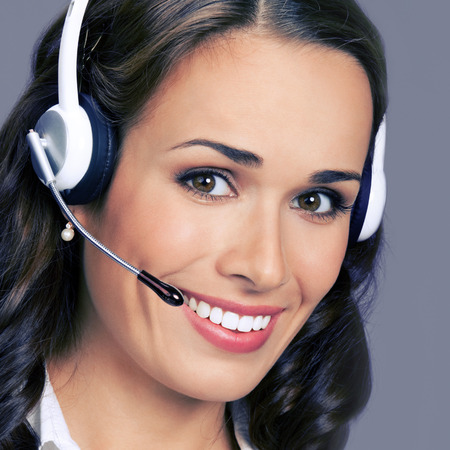 handsfree telephone: Cheerful customer support phone female operator in headset, posing at studio, over violet background