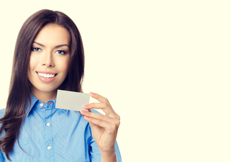 debet: Portrait of cheerful smiling businesswoman showing business or plastic credit card with blank copyspace for text or slogan message