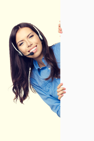 customer support: Portrait of happy smiling customer support phone operator in headset showing blank signboard with area for copyspace or product Stock Photo