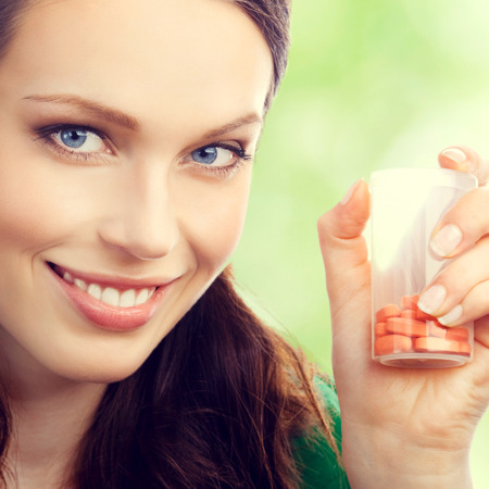 pills hand: Cheerful young lovely brunette woman showing bottle with pills, outdoor Stock Photo