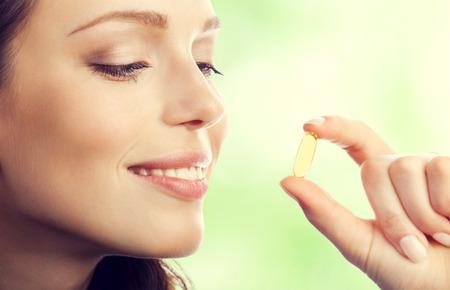 witaminy: Młoda uśmiechnięta piękna kobieta brunetka z Omega 3 kapsułki oleju z ryb, na zewnątrz