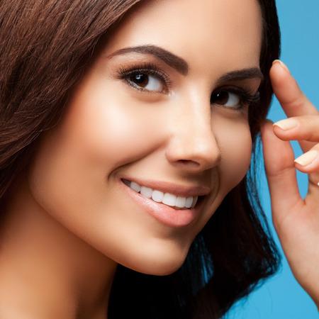 portrait studio: closeup portrait of beautiful smiling brunette woman, on blue background