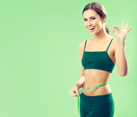 only 1 woman: Portrait of smiling young lovely woman in fitness wear with tape, showing okay gesture, over green background, with blank copyspace area for text or slogan
