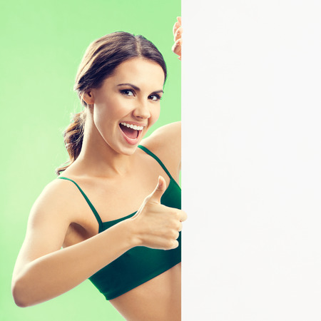 blank center: Portrait of smiling young lovely woman in fitness wear showing blank signboard with copyspace area for text or slogan, over green background