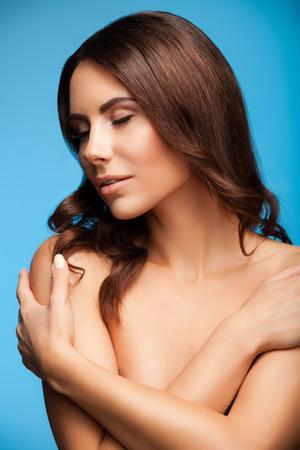 femme se deshabille: belle jeune femme avec les bras croisés sur sa poitrine, les épaules nues et les yeux fermés, sur fond bleu