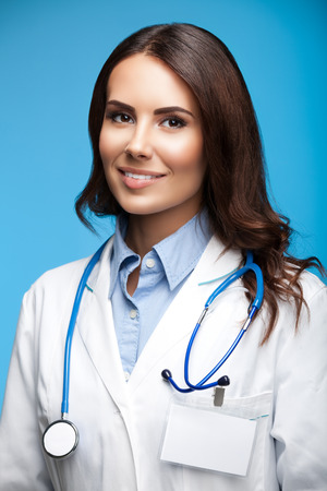 medicaid: Portrait of happy smiling female doctor, on blue background Stock Photo