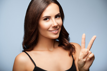 2 persons only: woman in black tank top clothing, showing two fingers or victory gesture, on grey background Stock Photo