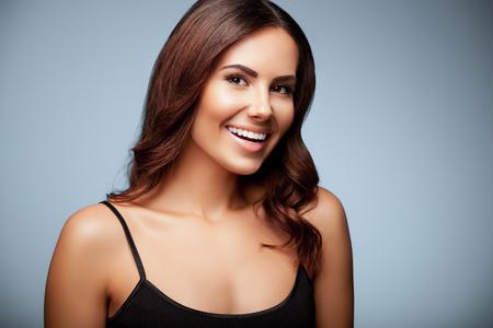 sonriente: retrato de la hermosa mujer joven sonriente en la ropa top negro, sobre fondo gris