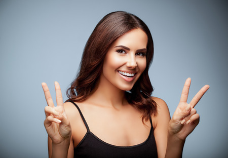 two persons only: Beautiful young woman in black tank top clothing, showing two fingers or victory gesture, on grey background Stock Photo