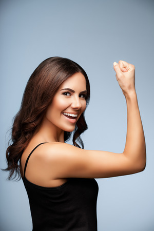 Portrait of cheerful smiling young woman happy gesturing, over grey background Stock Photo