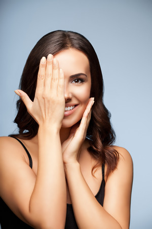 woman eye: smiling woman, with eye, clossed by hand, covering part of her face, over grey background