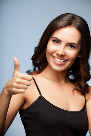 young woman smiling: Portrait of beautiful cheerful smiling woman showing thumb up hand sign gesture, over grey background