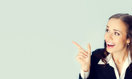 forefinger: Happy smiling brunette businesswoman showing blank copyspace area for slogan or text message