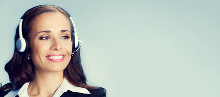 sales agent: Portrait of happy smiling customer support phone operator in headset, with blank copyspace area for slogan or text message