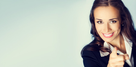 Portrait de jeune femme brune souriante affaires pointant du doigt spectateur, avec une zone de copyspace blanc pour slogan ou un message texte Banque d'images - 44407458