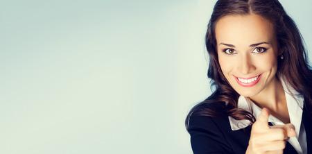 Portrait der jungen lächelnden Brunette Geschäftsfrau zeigt mit dem Finger auf Betrachter, mit leeren Copyspace Bereich für Slogan oder Textnachricht