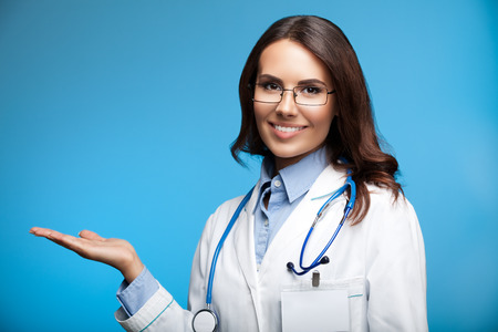 medicaid: Portrait of happy smiling young female doctor showing something or blank copyspace for slogan or text message, on blue background