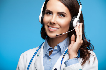 call: Portrait of happy smiling young doctor in headset, on blue background Stock Photo