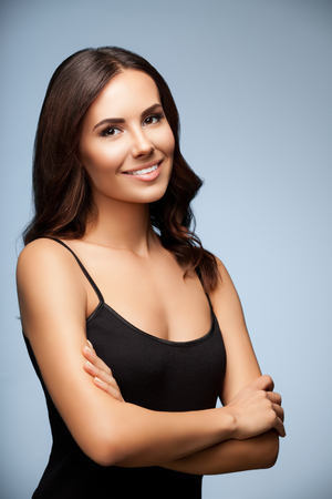 smiling: portrait of beautiful smiling young woman in black tank top clothing, on grey background Stock Photo