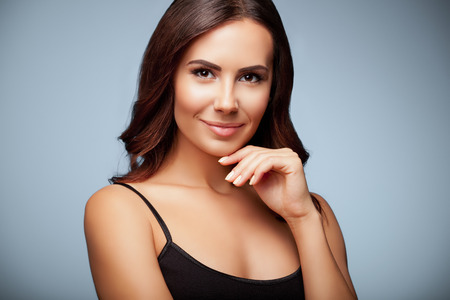 portrait of thinking young woman in black tank top clothing, on grey background 스톡 콘텐츠