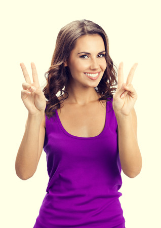 2 persons only: Happy smiling woman in casual smart lilac clothing, showing two fingers or victory gesture Stock Photo